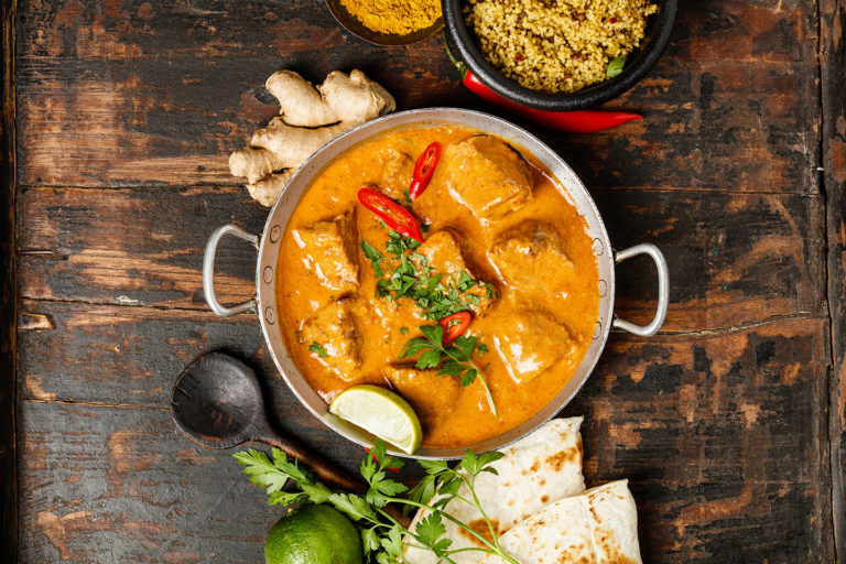 Traditional curry and ingredients on dark background. Curry, lime, ginger, chili, naan bread, rice, couscous, herbs and spices Flat lay